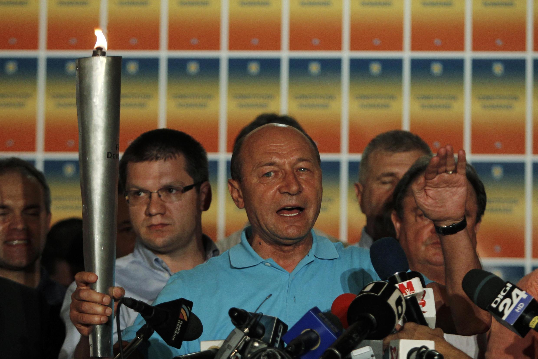 Le président roumain Traian Basescu brandit la « Torche de la démocratie » lors de son discours après les résultats du référendum, le 29 juillet 2012.