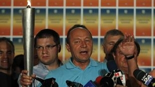 Tổng thống Rumani Traian Basescu cầm ngọn  « Đuốc Dân chủ » khi phát biểu sau khi có kết quả trưng cầu dân ý ngày 29/07/2012.