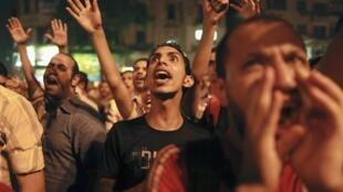 Manifestantes egípcios gritam slogans contra os candidatos Mohamed Mursi e Ahmed Chafiq na praça Tahrir, no Cairo, nesta segunda-feira.