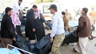 Servicios iraquíes retiran los cadáveres tras un atentado con coche bomba.