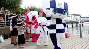 Las mascotas Miraitowa (en azul) y Someity (en rosa) con la karateka y campeona mundial Kiyou Shimizu en el desfile de presentación en la Odaiba Marine Park, Tokyo, 22 de julio 2020.