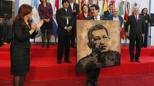 La Presidenta de Argentina aplaude en momentos en que entrega como regalo al Canciller venezolano, Nicolás Maduro, un retrato del Presidente Hugo Chávez, ausente de la cumbre, hecho por el artista argentino Norberto Filippo