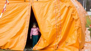 Une petite fille se tient devant un centre d'accueil temporaire de réfugiés à la frontière russo-norvégienne, le 13 octobre 2015.