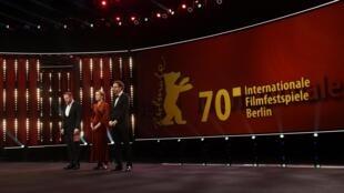 Os diretores da Berlinale, Carlo Chatrian e Mariette Rissenbeek, ao lado do ator Samuel Finzi (d) durante um minuto de silêncio.