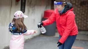 Una mujer desinfeta a una niña en Saint-Jean-sur-Richelieu, Quebec, el 11 de mayo de 2020.