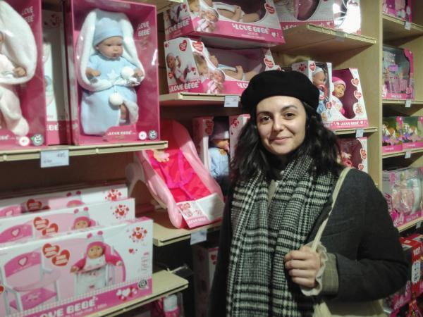 Joy Fleutot in front of dolls packaged in pink in a toy store in Strasbourg.