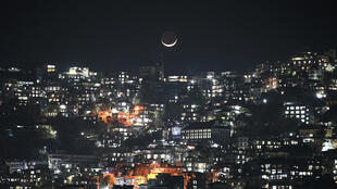 A crescent moon over homes on a hillside in Aizawl, capital of the northeastern Indian state of Mizoram
