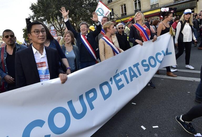 """Jean-Luc Mélenchon, deputado e líder de A França Insubmissa, de braços levantados e atrás da mensagem """"Golpe de Estado Social""""."""