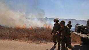 Des soldats israéliens arrivent pour éteindre un incendie près de la frontière avec la bande de Gaza, le 25 août 2020, déclenché par des ballons incendiaires lancés depuis l'enclave palestinienne.