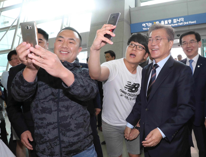 Le nouveau président sud-coréen Moon Jae-in pose pour des selfies à l'aéroport international d'Incheon, le 12 mai 2017.