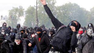 Le gaz lacrymogène flotte autour des manifestants masqués, les Black Blocs lors d'affrontements avec la police anti-émeute CRS française, pendant le défilé du 1er-Mai à Paris, en France.