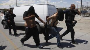 Dos hombres, sospechosos de haber asesinado a una mujer policía, escoltados por agentes policiales en Ciudad Juárez, el 8 de agosto de 2013.
