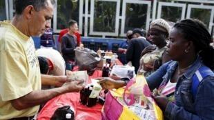 Venezuelanos no mercado de rua de Caracas.