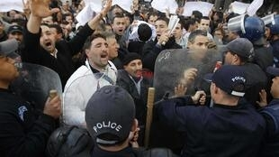Protesters chant slogans in front of a policeman during a demonstration in Algiers on 19 February