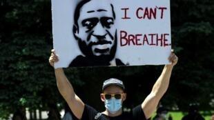 """Un manifestant porte une pancarte à l'effigie de George Floyd, le 30 mai 2020 à Denver, dans le Colorado, avec ses derniers mots: """"Je ne peux pas respirer""""."""