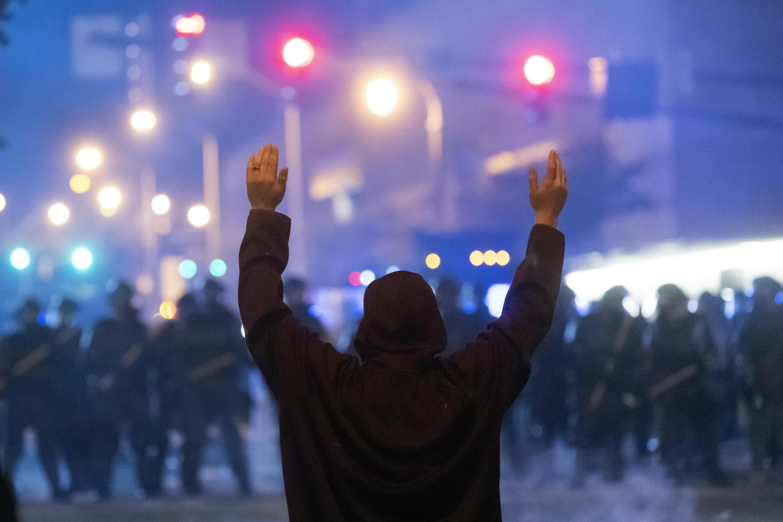 Un manifestante alza sus brazos ante la policía antidisturbios durante una protesta contra el racismo el 29 de mayo de 2020 en la ciudad estadounidense de Atlanta