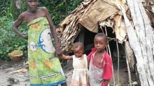 Une grand-mère autochtone et ses petits enfants devant leur hutte dans la Sangha au nord du Congo.
