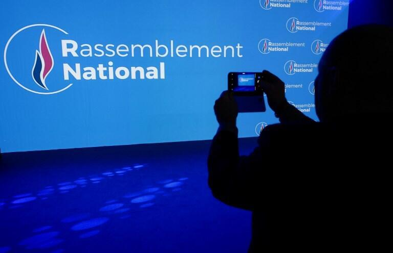 A person takes a picture of the new name of the far-right party National Front (FN) after party members backed the changing of the name to National Rally in Lyon on June 1, 2018.