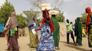 Wanawake wakipokea chakula kutoka kwa shirika la Mpango wa Chakula Duniani, WFP katika kambi ya wakimbizi wa ndani ya Banki, katika jimbo la Borno, Nigeria, Aprili 26, 2017.