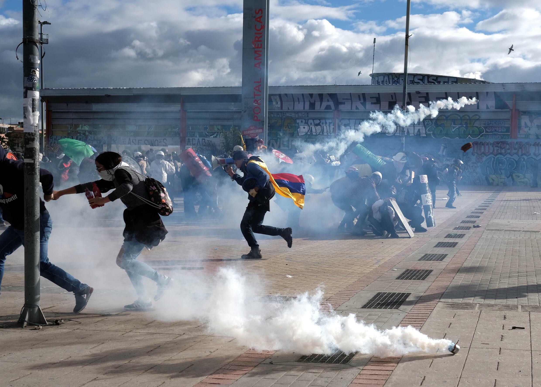 Manifestantes se escudan ante lanzamiento de gases por parte de la Policía en medio de las protestas en el día de la independencia de Colombia.