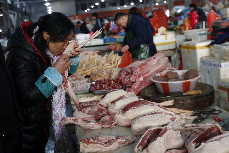 Chọn mua thịt vịt tại một chợ ở Chiết Giang, 14/02/2014.