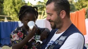 Une jeune fille haïtienne dans les bras d'un bénévole argentin, le 21 janvier 2010.