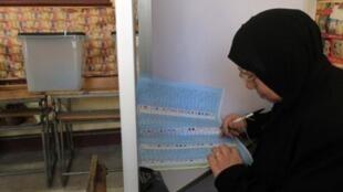 Le Caire, 29 janvier 2012. Une Égyptienne en train de sélectionner ses favoris pour la Choura, dans un «isoloir»