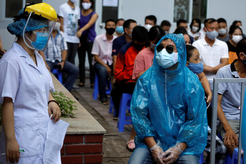 Những người trở về từ Đà Nẵng xếp hàng chờ xét nghiệm COVID-19, tại một trung tâm xét nghiệm ở Hà Nội. Ảnh chụp ngày 10/08/2020.
