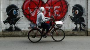 Une photo prise le 11 janvier 2019 sur laquelle on peut voir un graffiti sur un mur à Bangkok avec le mot «vote», couvert de fil de fer barbelé.