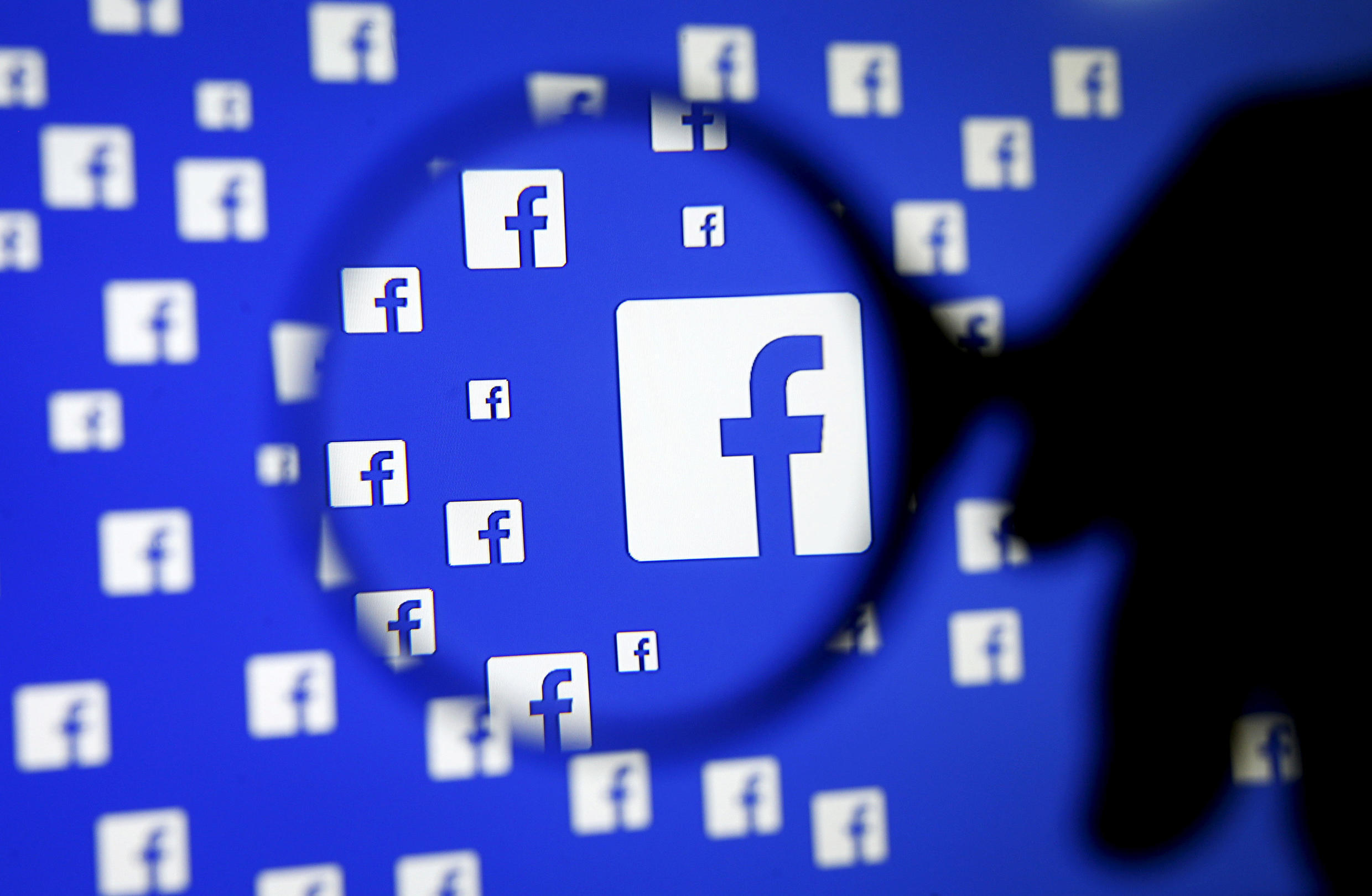 A man poses with a magnifier in front of a Facebook logo on display December 16, 2015.