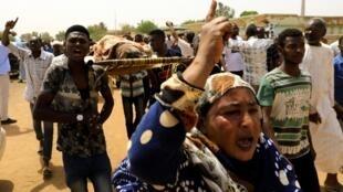 Multidão transporta um corpo no Sudão a 1 de Julho de 2019.