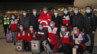 Des médecins chinois posent à leur arrivée à Rome, le mardi 13 mars 2020, alors qu'ils viennent en soutien aux médecins italiens.