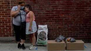 Sandra Cruz, qui a perdu son emploi à cause du Covid-19, a 4 mois de retard sur son loyer et craint d'être expulsée. Elle et sa fille Gabriella attendent leur tour pour récupérer des produits d'épicerie gratuits distribués par le Chelsea Collaborative.