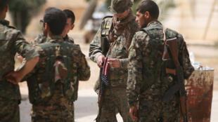 Một binh sĩ Mỹ bên cạnh các binh sĩ thuộc Lực Lượng Dân Chủ Syria, tại Raqa, ngày 27/05/2016.