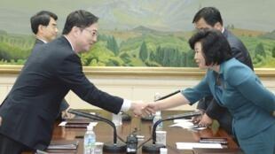 Trường đoàn đàm phán Hàn Quốc Chun Hae-sung (T) bắt tay đồng nhiệm Bắc Triều Tiên Kim Song-hye, tại cuộc gặp ở Bàn Môn Điếm, ngày 12/06/2013