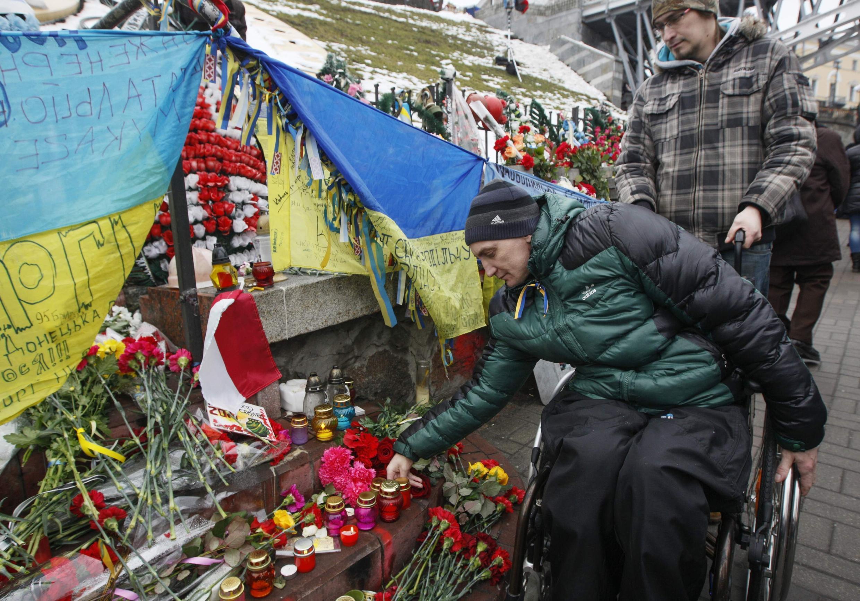 Один из участников Евромайдана возлагает цветы во время памятной церемонии у площади Независимости в Киеве 20 февраля 2015.