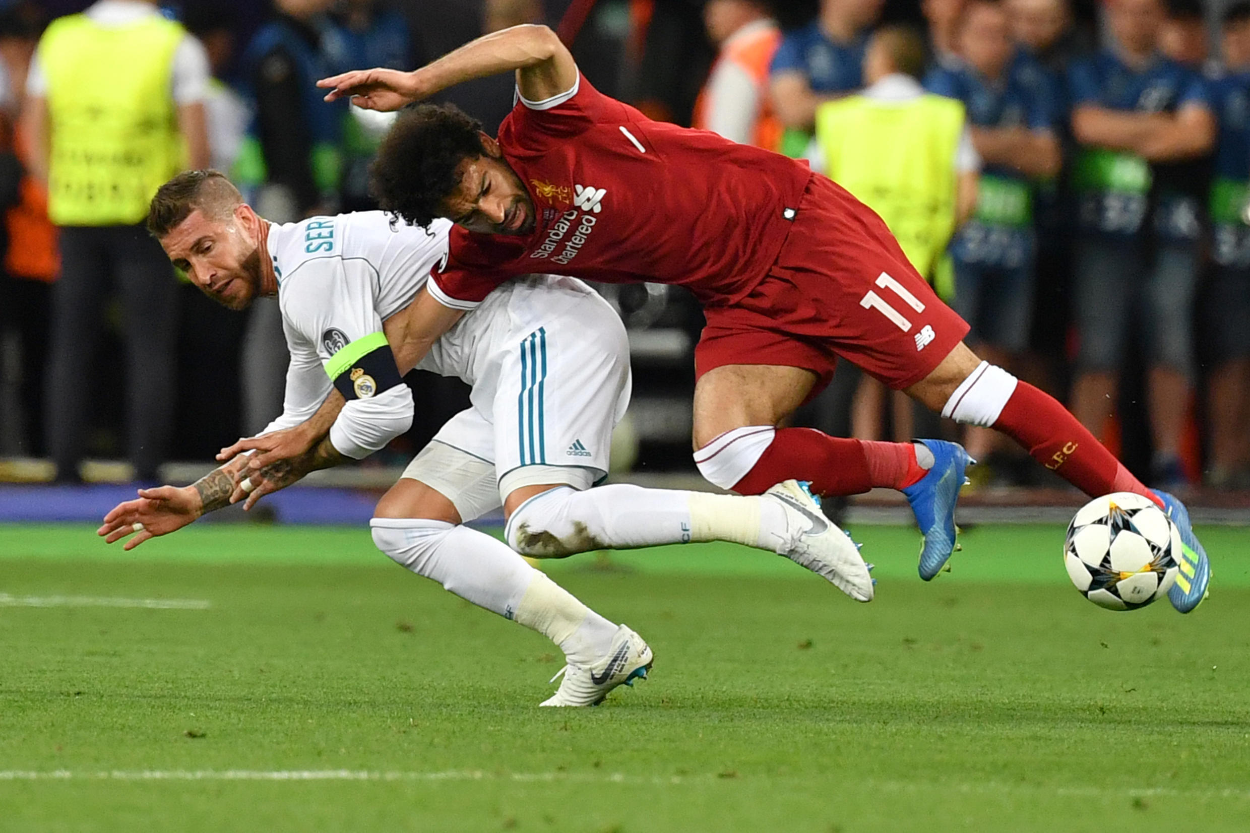 Mo Salah (right) is pulled to the ground by Sergio Ramos leading to a dislocated shoulder during the 2018 Champions League final in Kiev
