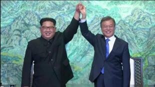 O líder norte-coreano, Kim Jong-un (esquerda), e o presidente sul-coreano, Moon Jae-in, levantam os braços em sinal de triunfo pelo encontro histórico entre os dirigentes das duas Coreias.