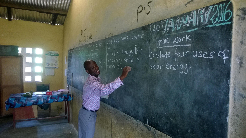 A teacher writes on the blackboard at Akroso school, Central Region, Ghana
