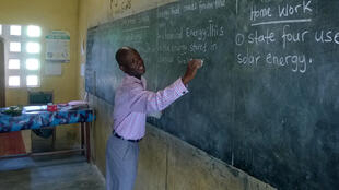 A teacher writes on the blackboard at Akroso school, Central Region, Ghana