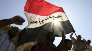 """Des supporters brandissent le drapeau égyptien, sur lequel on peut lire l'inscription """"Egypte je t'aime"""". Khartoum, le 17 novembre 2009."""
