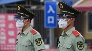 Des agents de la police paramilitaire chinoise bloquent à l'entrée du marché de gros de Xinfadi au sud de Pékin, le 13 juin 2020.