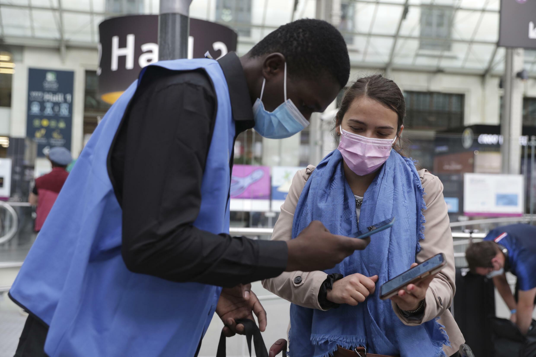 8月9日巴黎里昂火车站,检查乘客新冠健康码的工作人员。