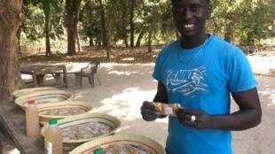 Paterne Diamacoune et les six variétés de noix de cajou transformées dans l'exploitation, à Singalene (Sud du Sénégal).