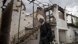 Un homme passe devant une maison détruite après l'opération «antiterroriste», à Kumanovo, le 11 mai 2015.