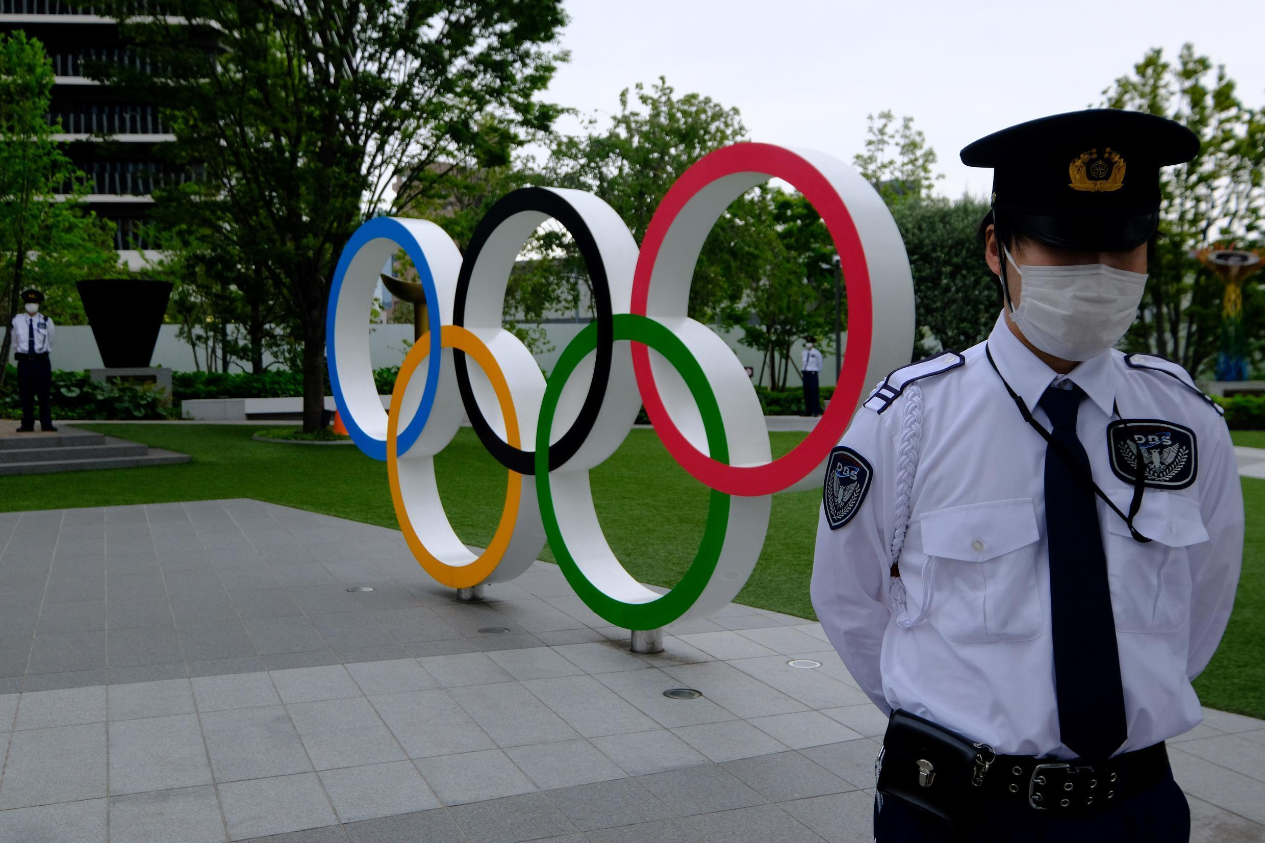 Security guards keep watch next to the Olympic Rings while people take part in a protest against the hosting of the 2020 Tokyo Olympic Games, in front of the headquarters building of the Japanese Olympic Committee in Tokyo, on May 18 2021