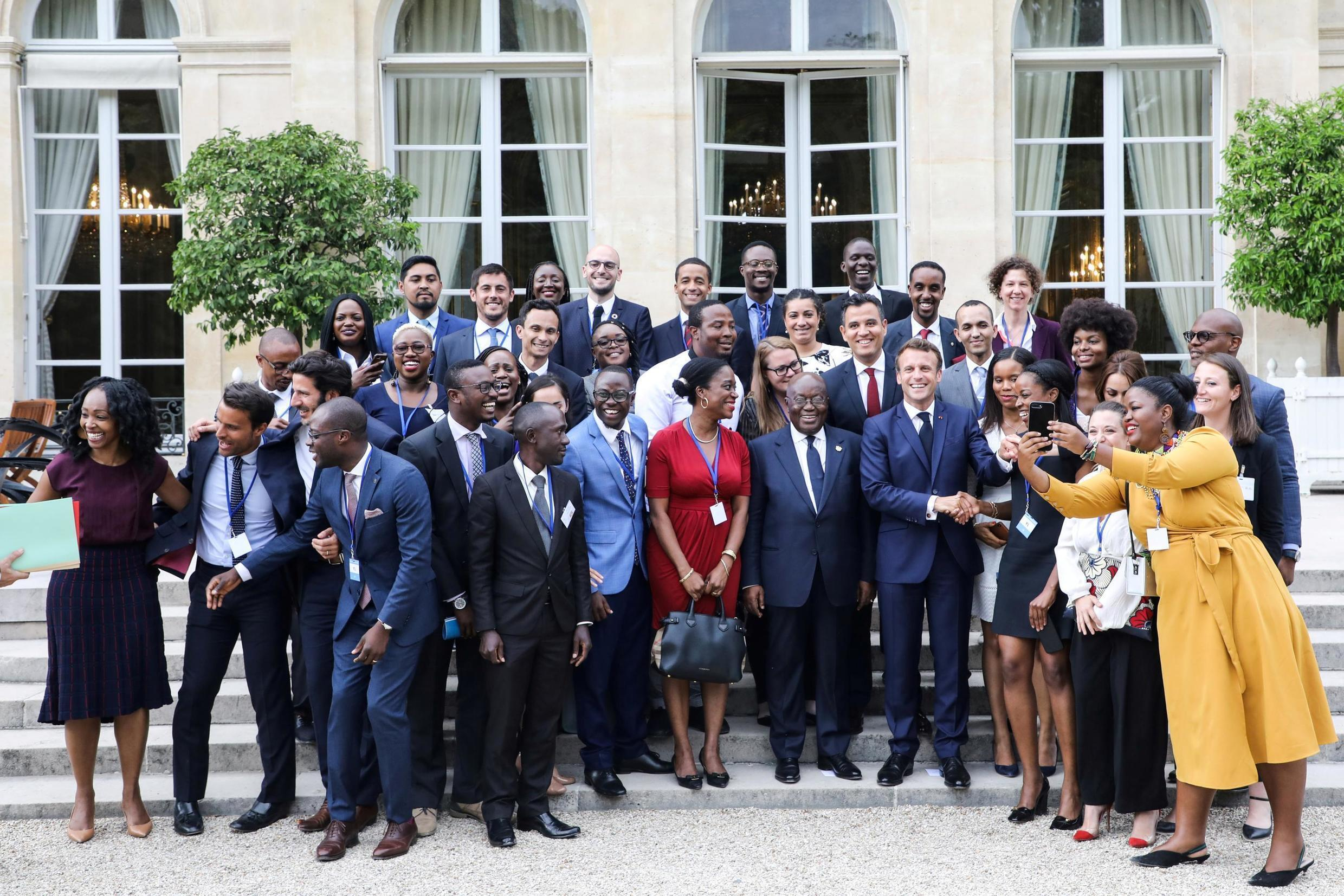 """French President Emmanuel Macron and Ghanaian President Nana Akufo-Addo pose with members of the African diaspora at the Elysee presidential palace after a debate entitled """"Parlons d'Afrique"""" (Let's talk about Africa) France July 11, 2019."""