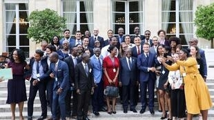 "French President Emmanuel Macron and Ghanaian President Nana Akufo-Addo pose with members of the African diaspora at the Elysee presidential palace after a debate entitled ""Parlons d'Afrique"" (Let's talk about Africa) France July 11, 2019."