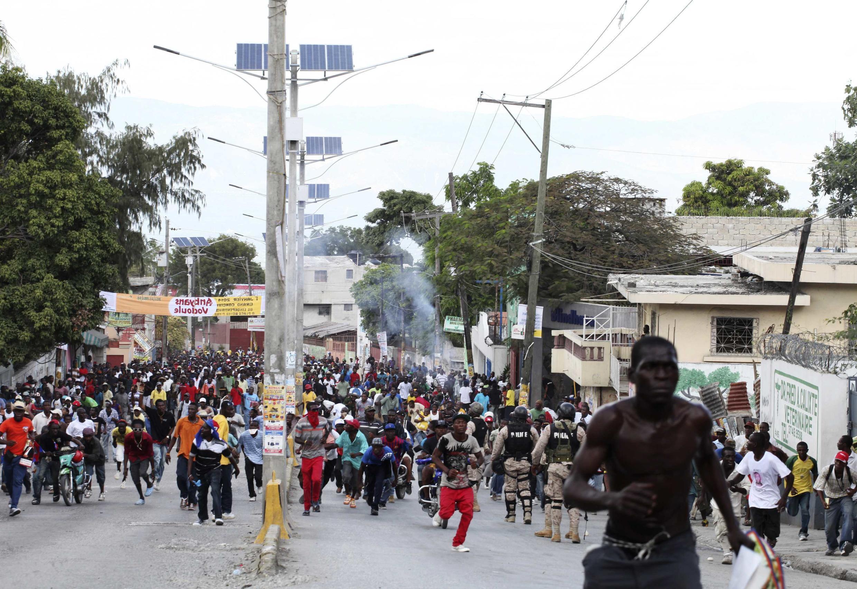 Des manifestants fuyant les violences dans les rues de Port-au-Prince, le 18 novembre 2013.