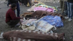 Les corps de Syriens tués après une frappe aérienne du régime de Bachar el-Assad, dans le quartier al-Maysar d'Alep, le 18 janvier 2014.